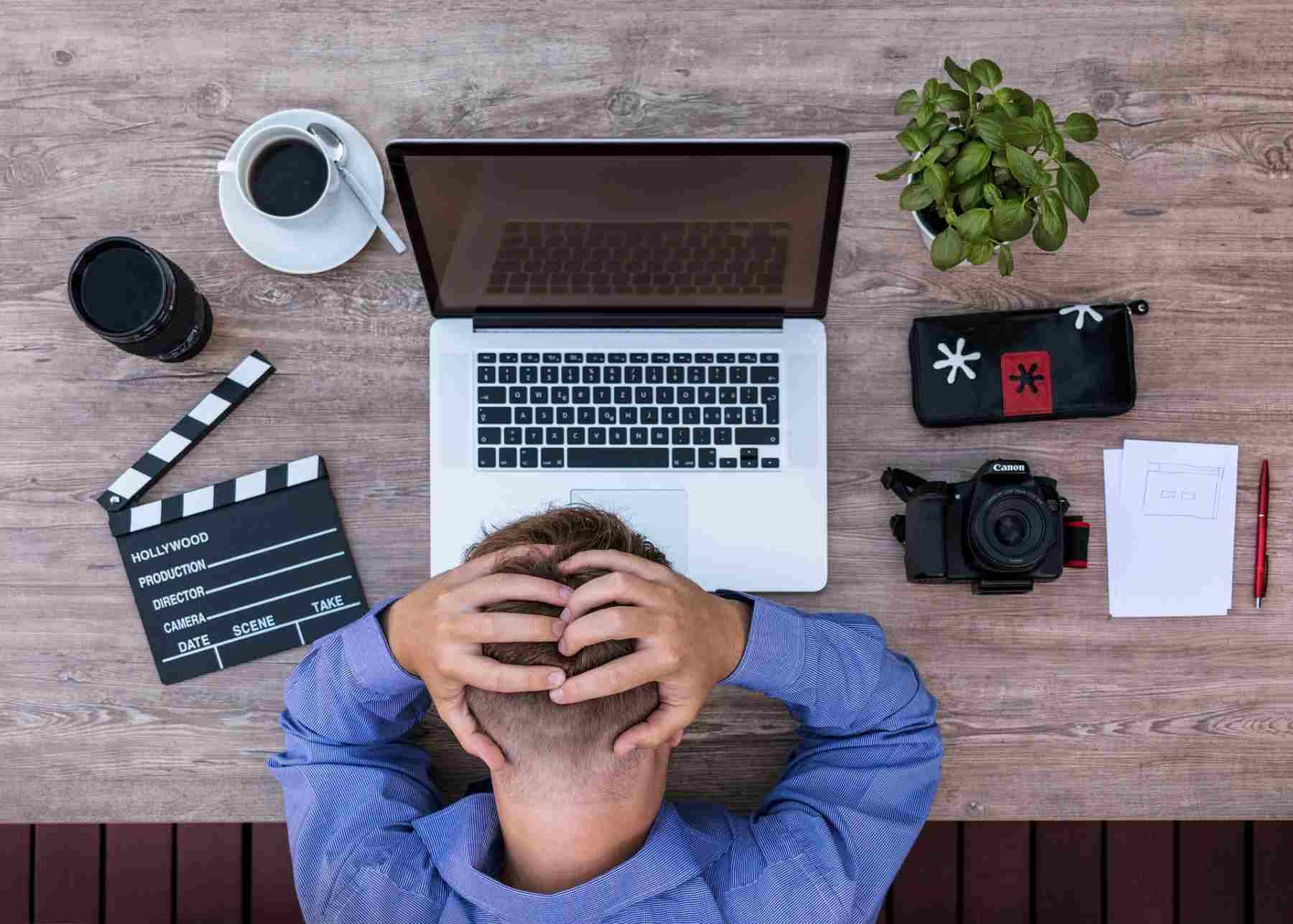 Tipps gegen Haarausfall | Stress als Auslöser für Haarausfall | Digitalarbeiter hält sich verzweifelt den Kopf vor dem Laptop